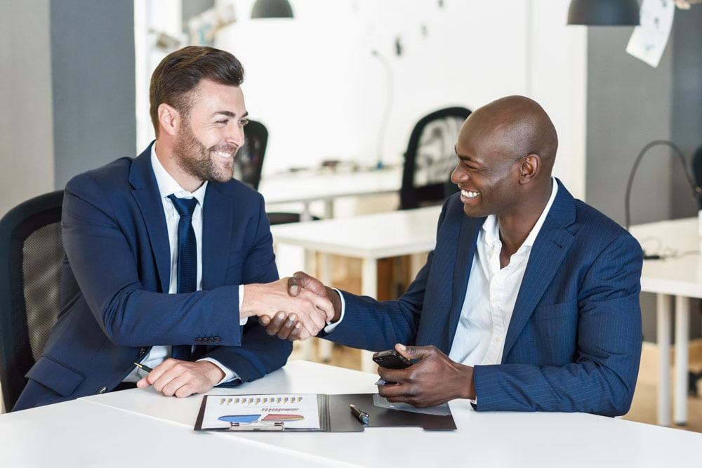 Two professional coworkers shaking hands while smiling.